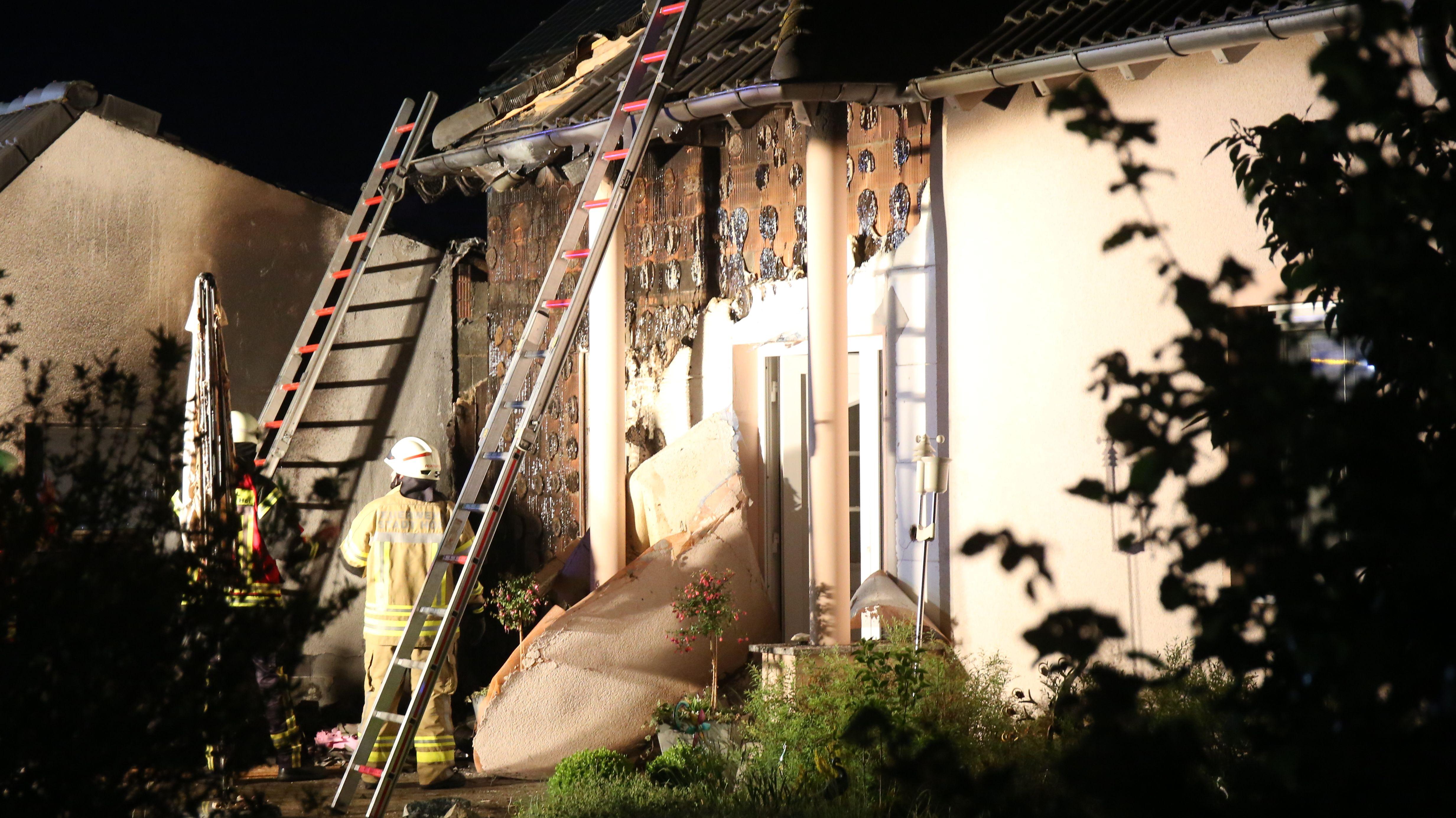 Feuerwehrmänner stehen vor dem Haus und haben Leitern zum Dachstuhl aufgestellt. Die Wand des Hauses ist verbrannt.