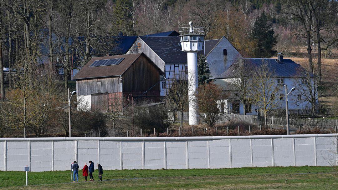 Die Mauer und ein Wachturm stehen mitten in dem ehemals geteilten Dorf Mödlreuth.