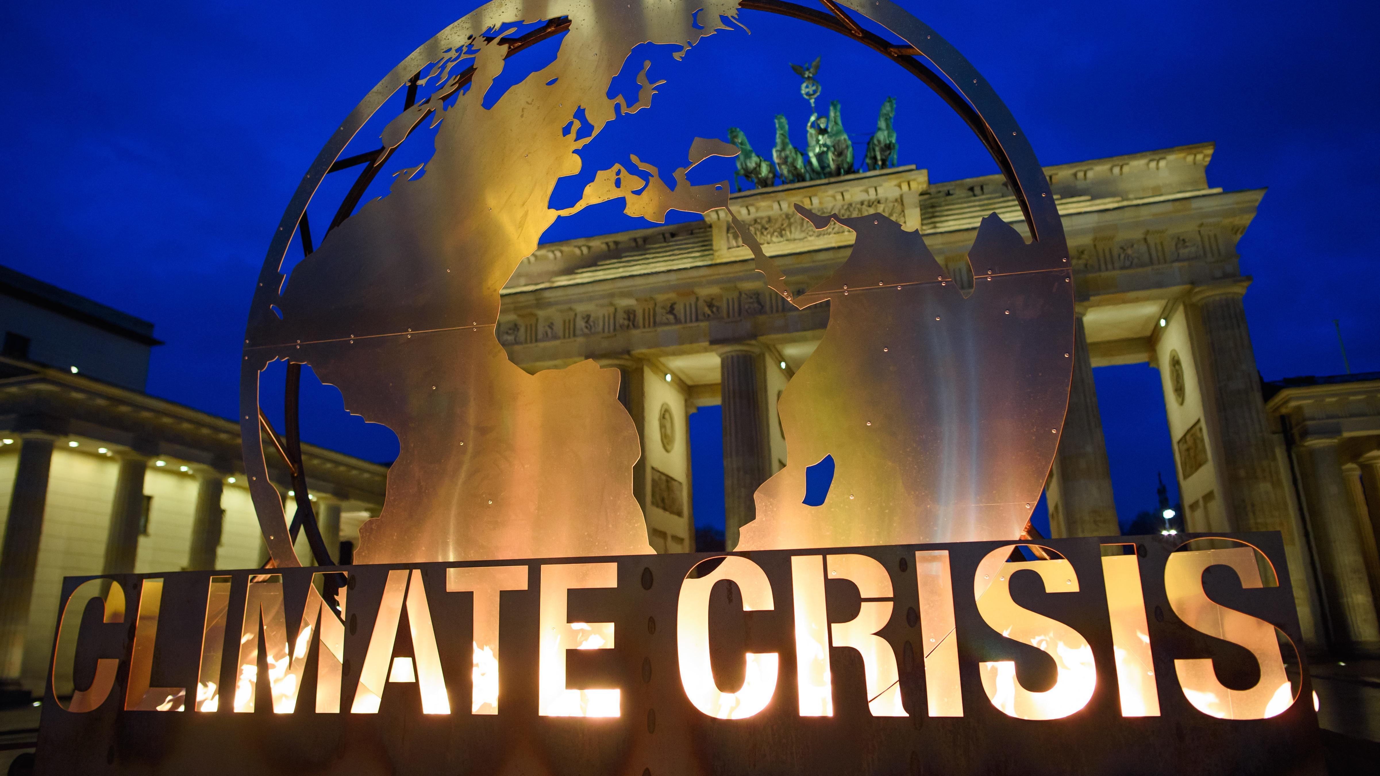 """Weltkugel mit dem Schriftzug """"Climate Crisis"""" vor dem Brandenburger Tor."""