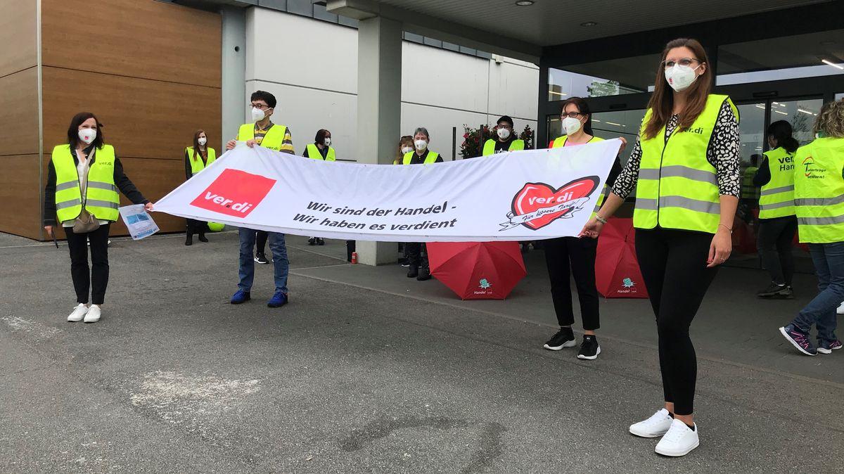 """Mitarbeiter stehen mit Warnwesten vor einer Supermarktfiliale und halten ein Transparent mit der Aufschrift """"Wir sind der Handel - Wir haben es verdient"""" hoch."""