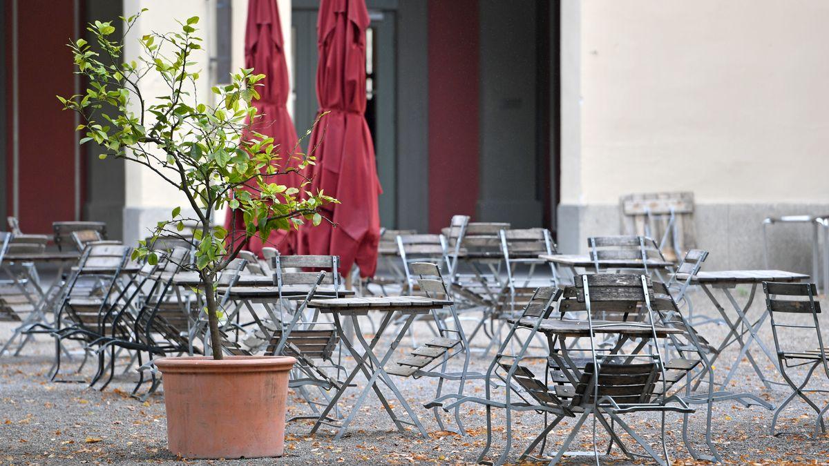 Leere, unbesetzte freie Stühle und Tische im Außenbereich eines Restaurants in München.