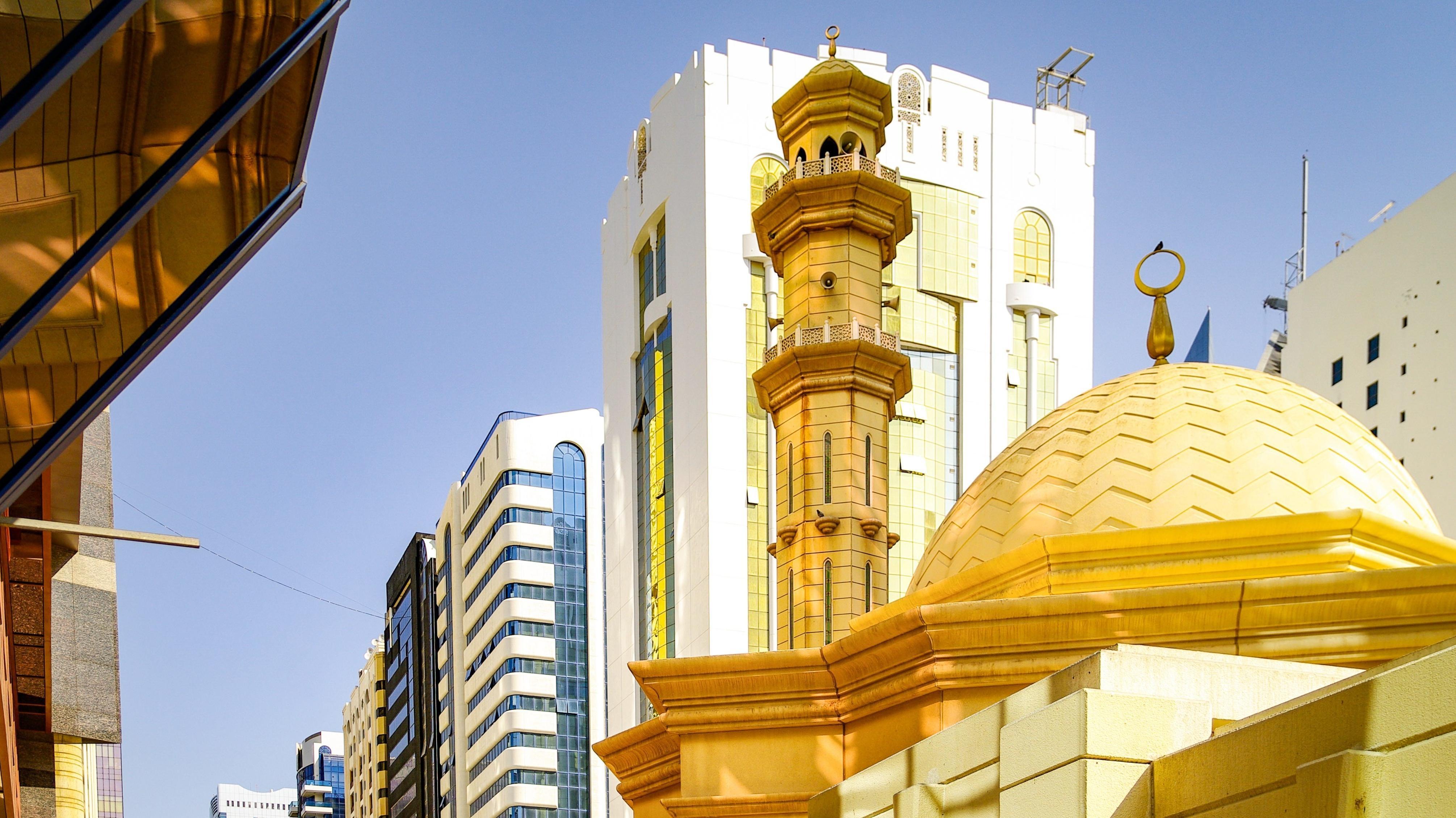 Eine kleine Moschee steht inmitten von Hochhäusern der architektonisch hochmodernen Metropole Abu Dhabi.