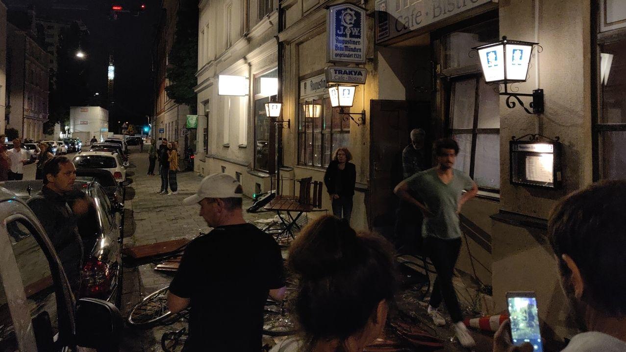 Menschen betrachten die Zerstörungen vor dem Lokal im Münchner Westend.