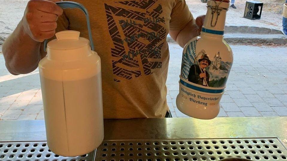 Ein junger Mann hält eine mit Bier gefüllte Milchkanne in der Hand