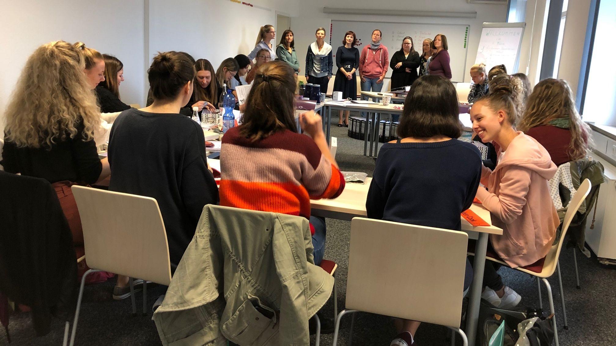 Mehrere Frauen sitzen und stehen um Tische herum.