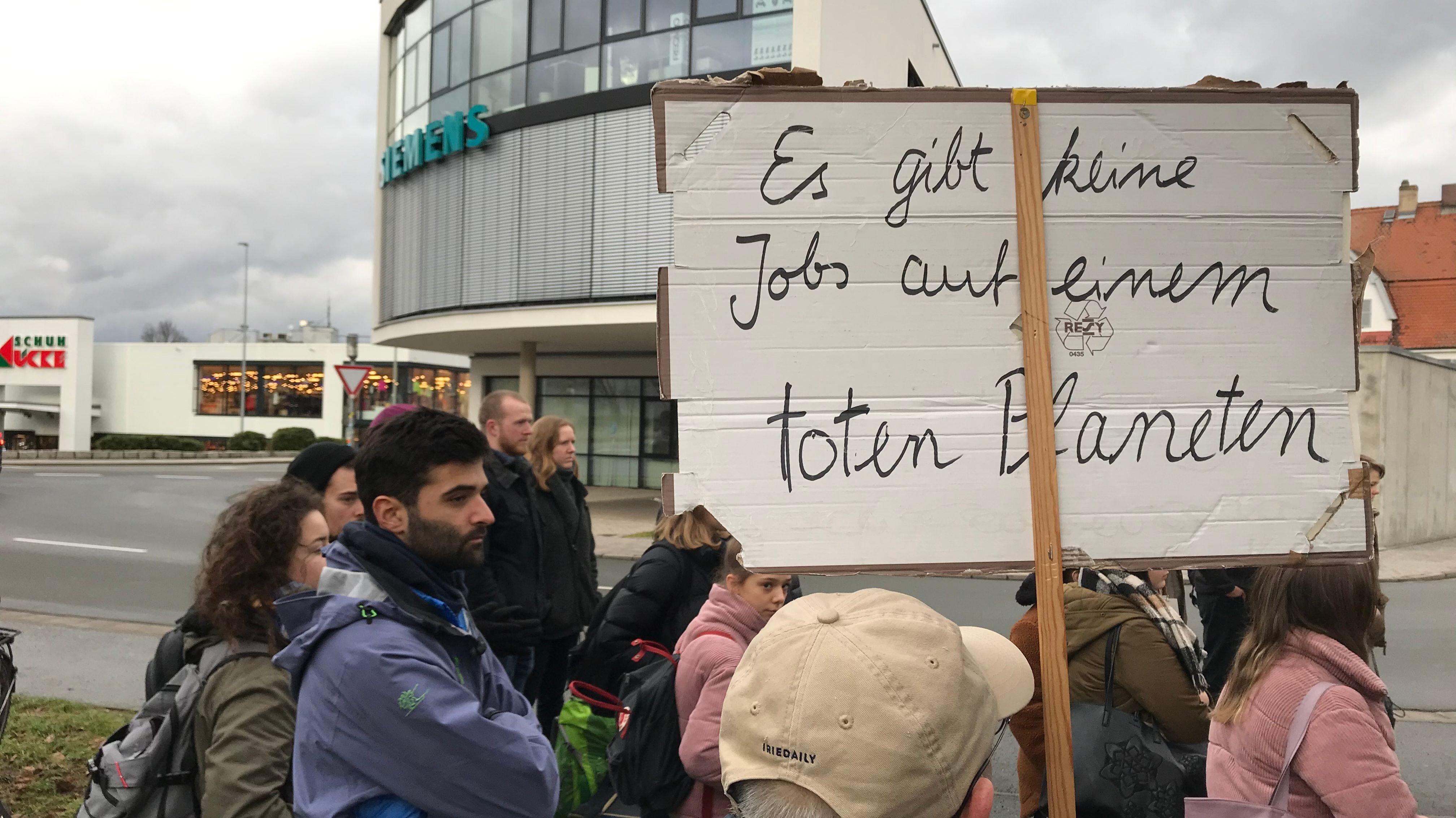 """Demonstranten stehen in Bayreuth vor der Siemens-Niederlassung und halten ein Transparent mit der Aufschrift """"Es gibt keine Jobs auf einem toten planten"""" in die Höhe."""
