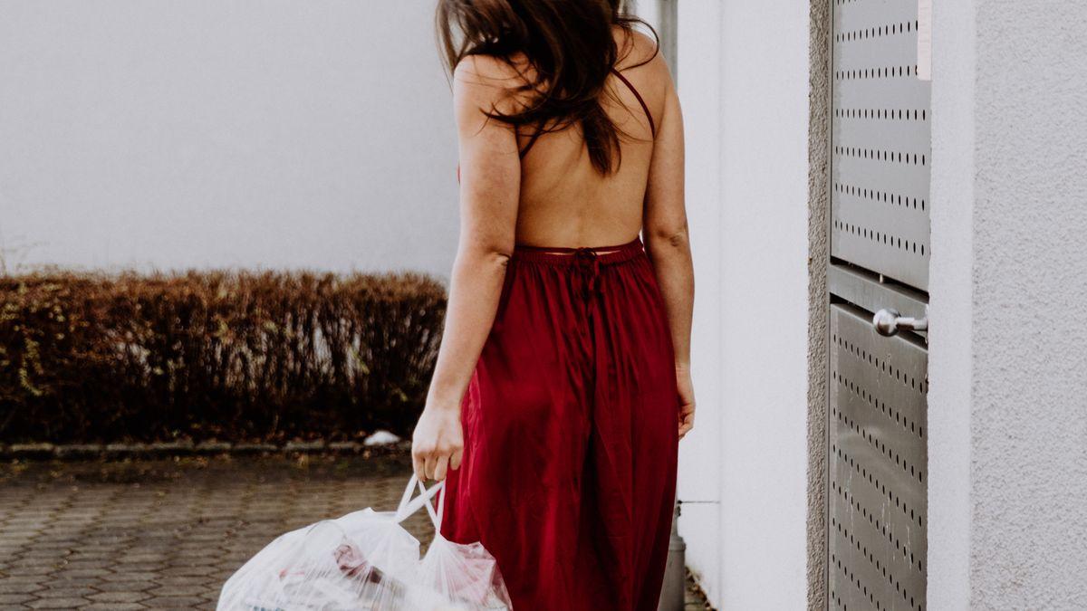 Frau in rotem rückenfreiem Kleid bringt den Müll raus.