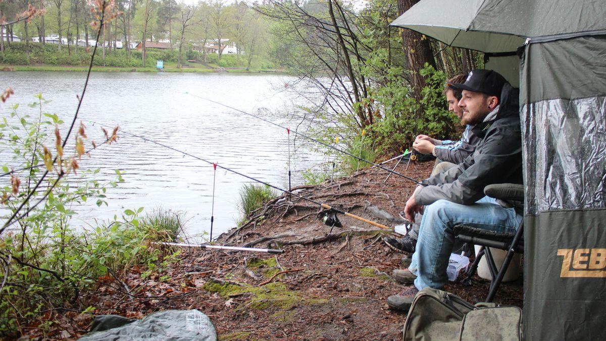 Zwei Männer sitzen unter einem Regenschirm am Seeufer.