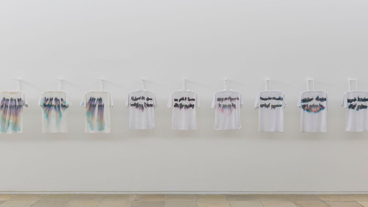 Weiße T-Shirts hängen nebeneinander in einer Reihe an weiße Wand im Haus der Kunst.