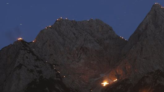 Viele kleine Bergfeuer auf der Bergkette rund um das Zugspitzdorf Grainau