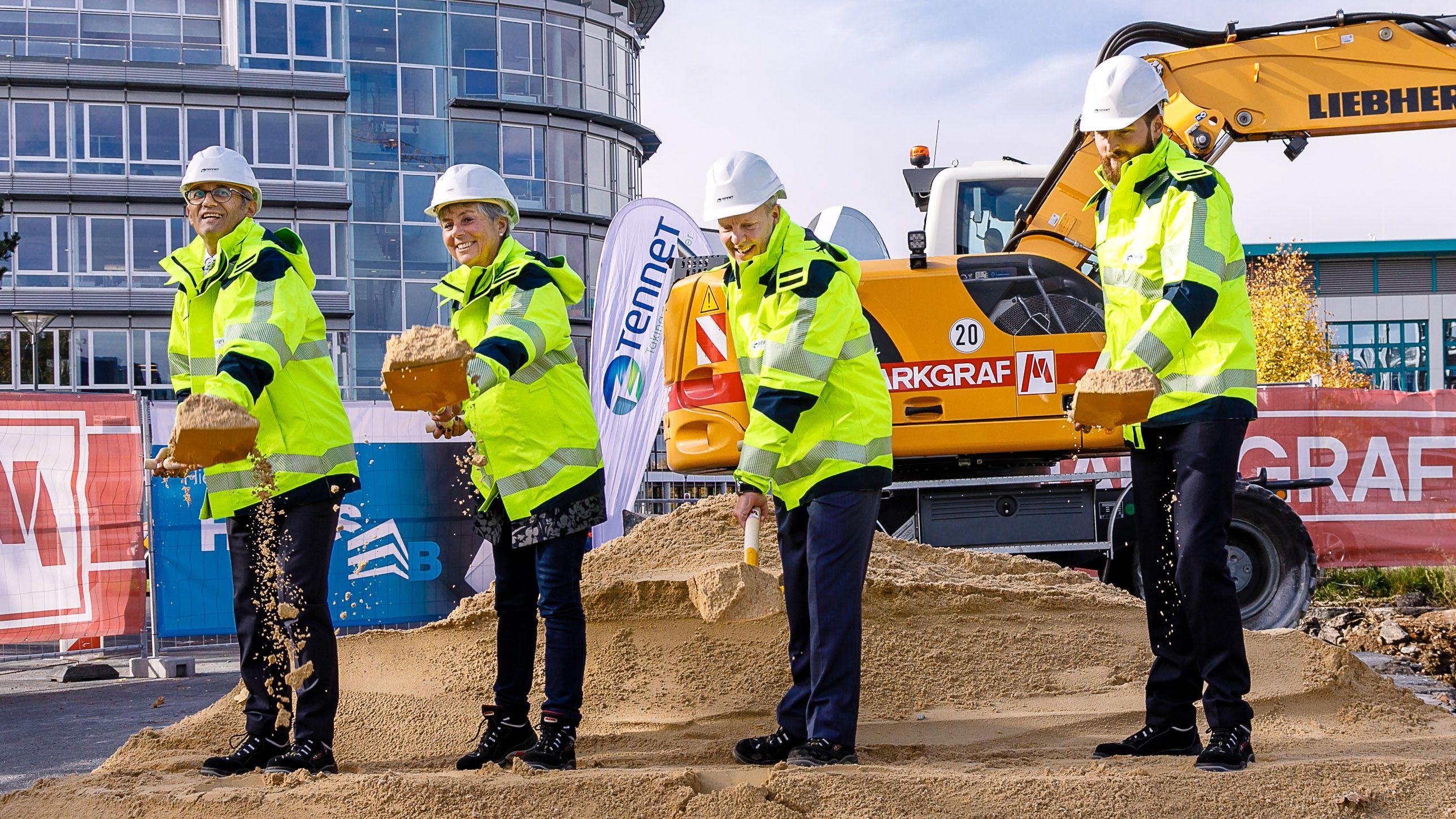 Politiker und Funktionäre stehen mit Spaten auf einer Baustelle und werfen Sand.