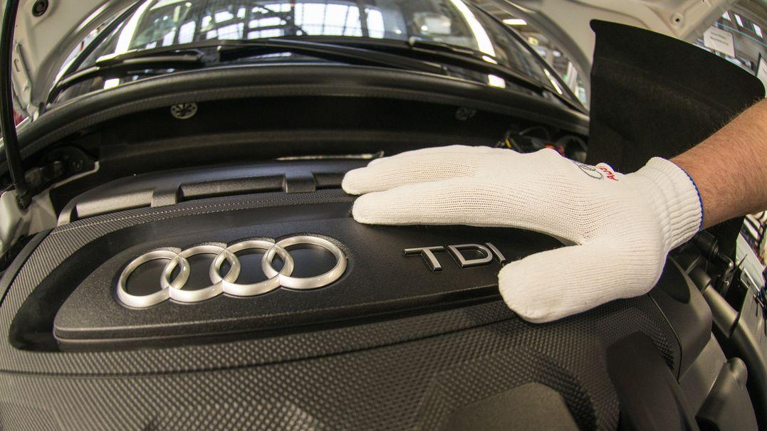 Nahaufnahme eines Motors mit dem Audi-Logo, vier ineinander greifende Ringe. Darauf liegt eine Hand in weißem Arbeitshandschuh.