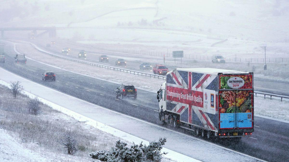Ein Lastwagen vom Discounter Aldi fährt während eines Schneesturms auf der M6 bei Shap in Cumbria.
