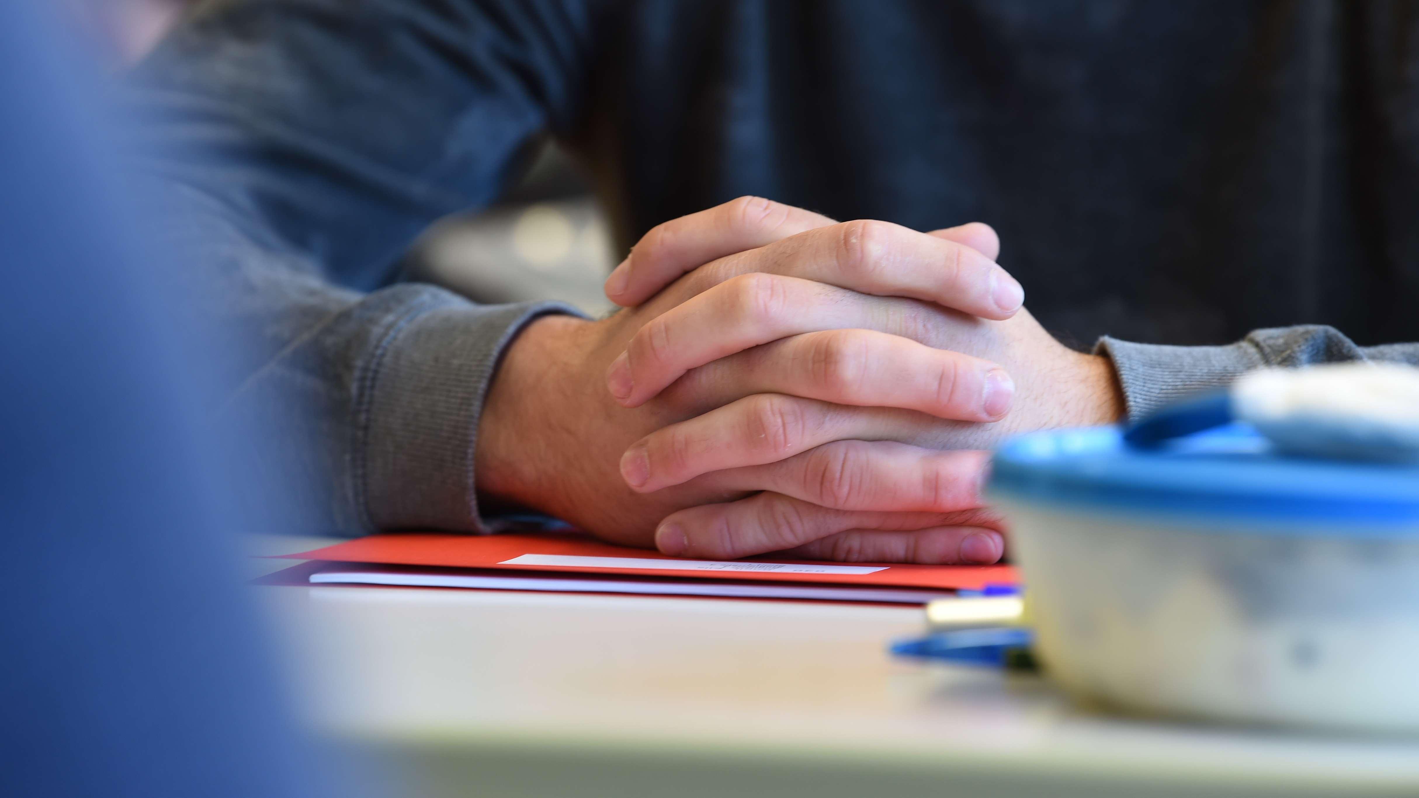 Ein Abiturient faltet vor Beginn der Abiturprüfung im Fach Deutsch die Hände