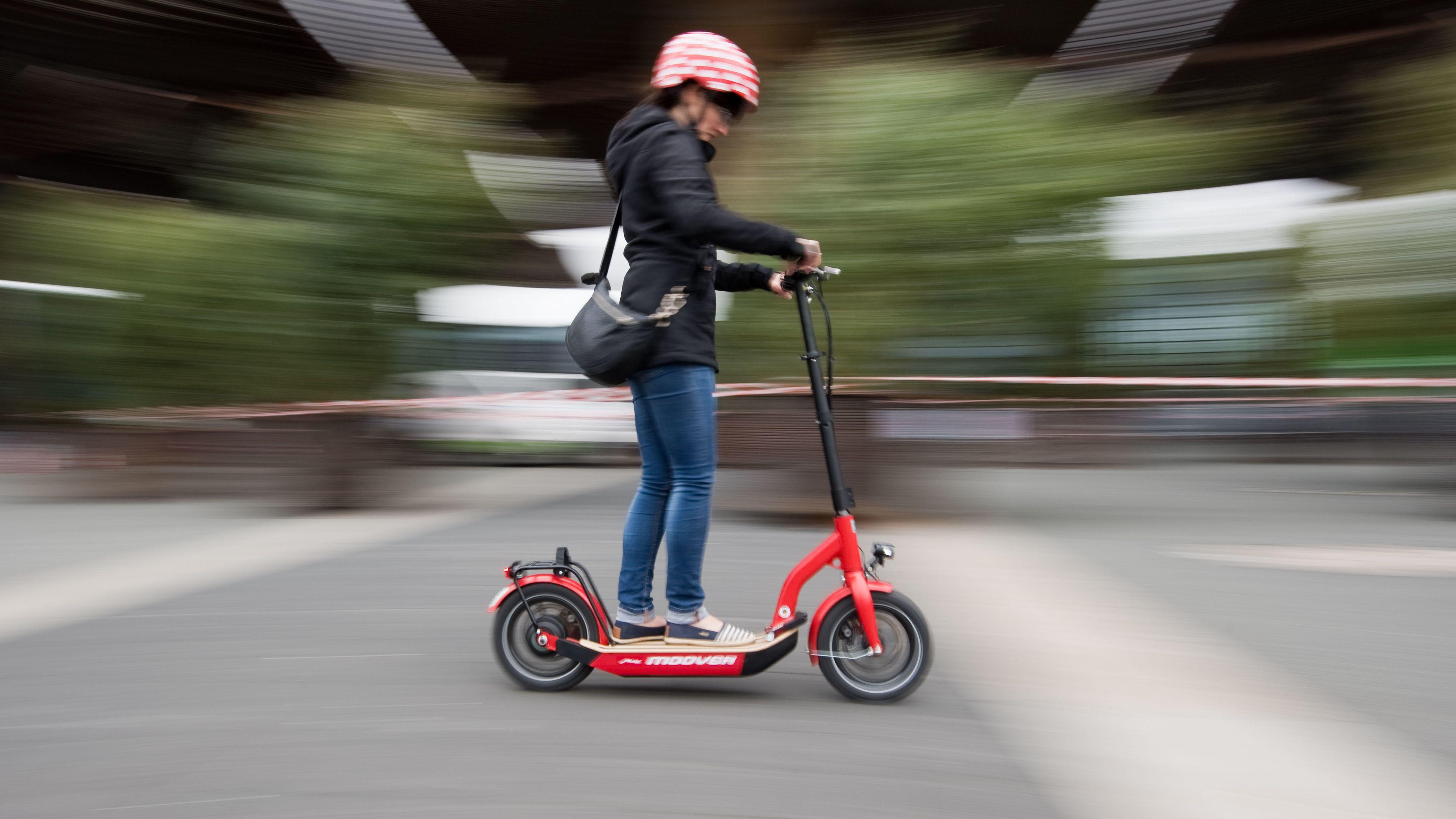 Eine Frau fährt mit einem E-Scooter