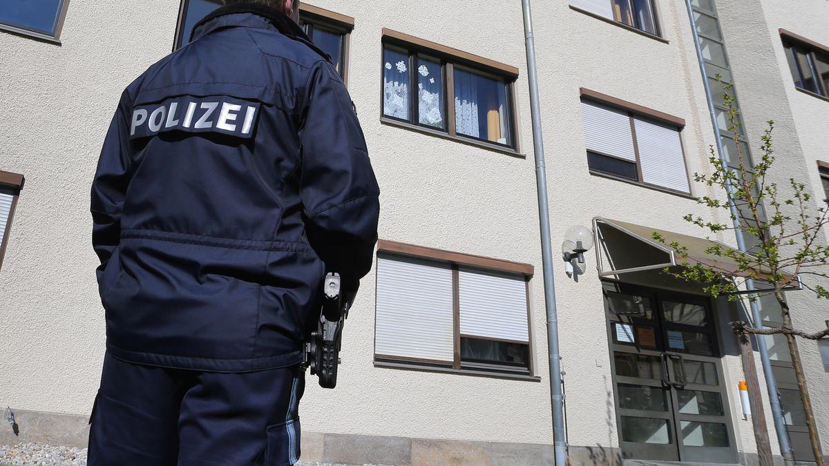 Ein Polizist steht vor einem Wohnhaus