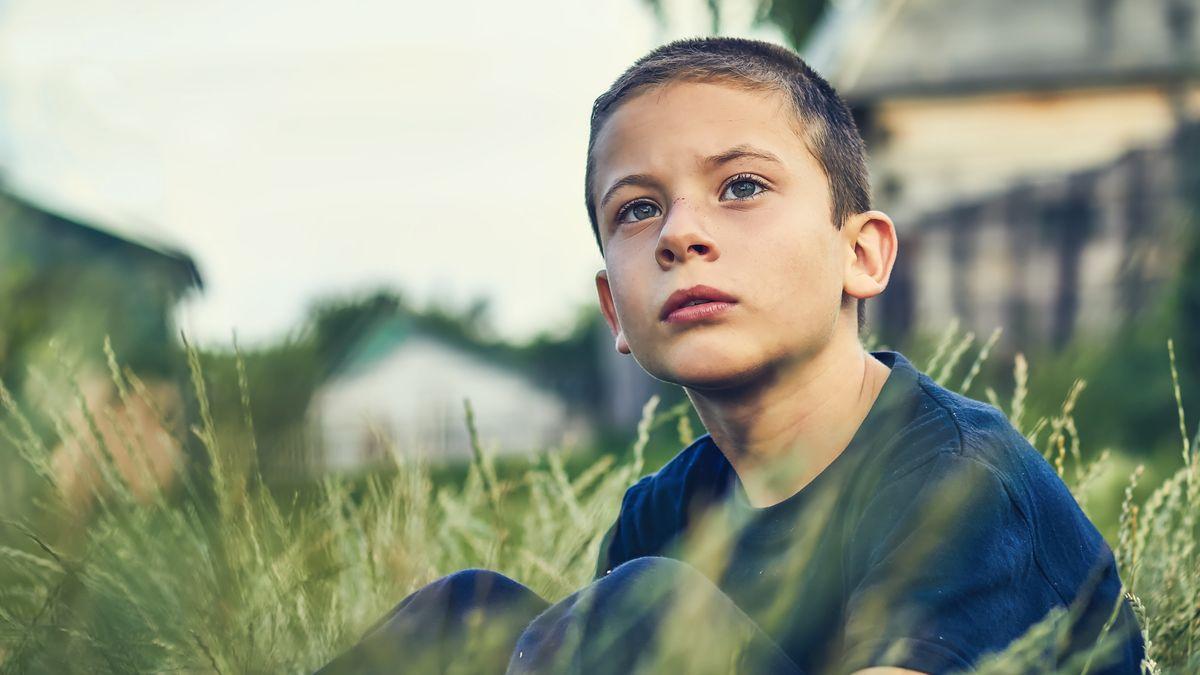 Junge sitzt in einer Wiese und schaut nachdenklich in die Ferne.