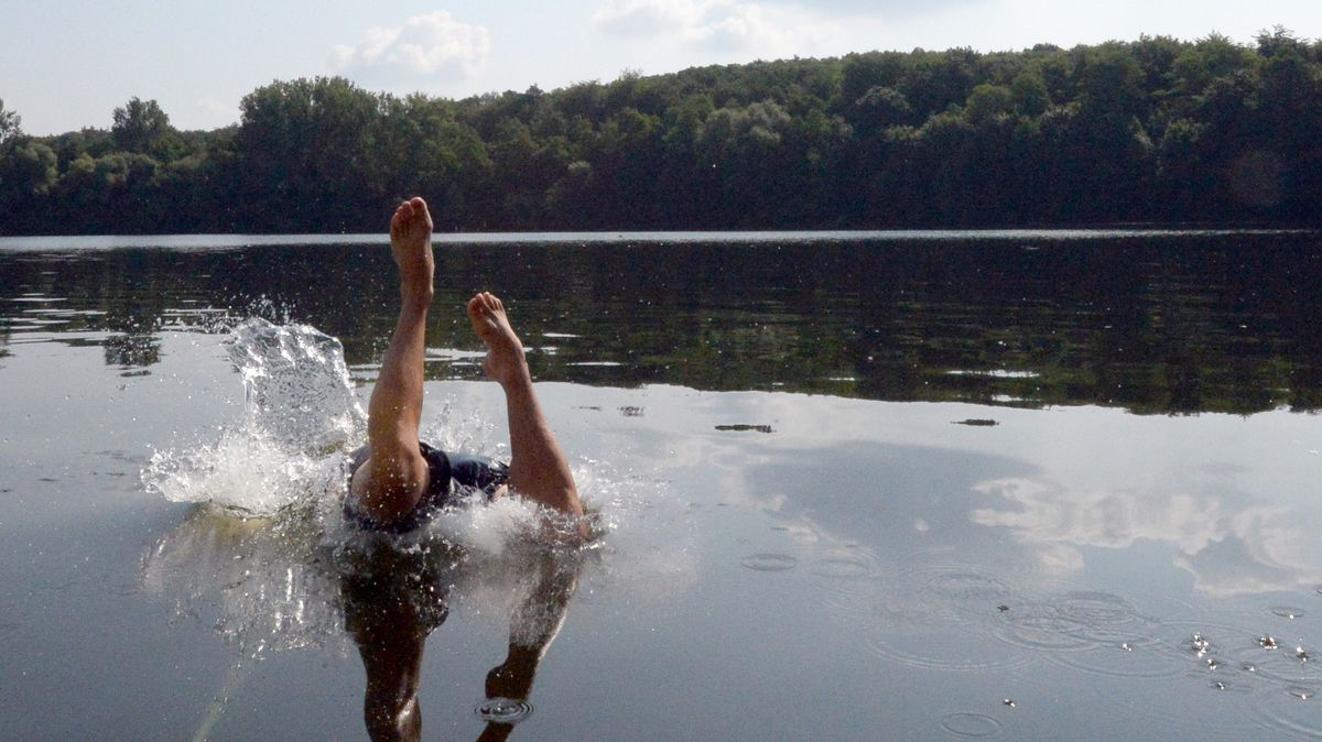 Mann springt in einen Badeweiher (Symbolbild).