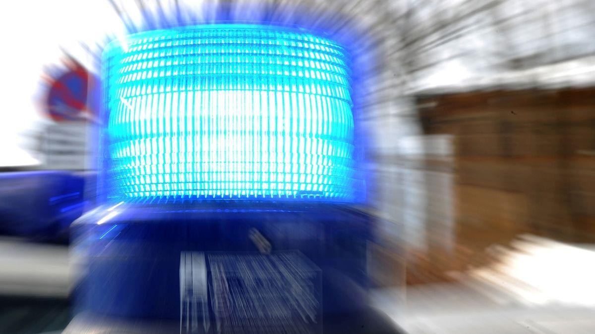 Ein Blaulicht auf einen Polizeiauto, im Hintergrund ein Verkehrszeichen.