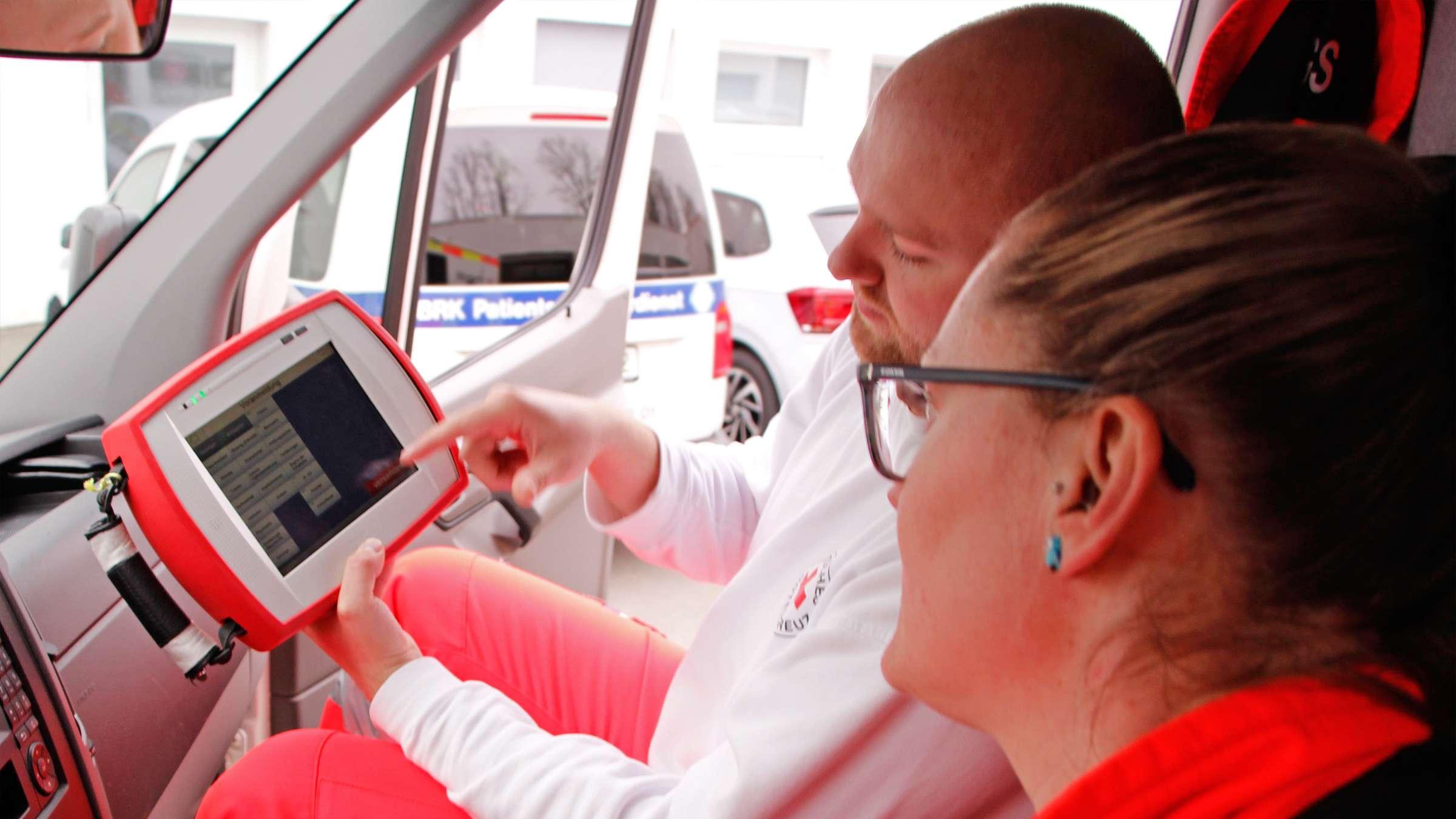 Zwei Sanitäter sitzen in einem Krankenwagen und bedienen ein Tablet.
