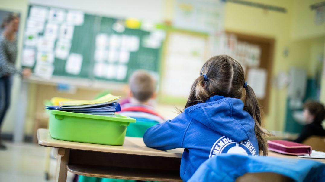 Schülerinnen und Schüler einer Grundschule sitzen mit Abstand in ihrem Klassenraum.