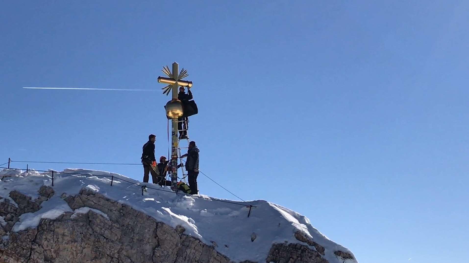 Schlosser arbeiten am Gipfelkreuz der Zugspitze