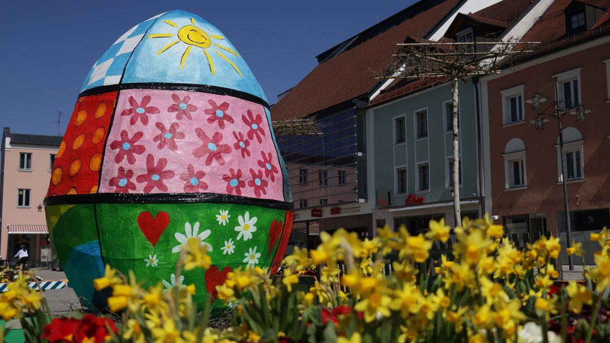 Zwischen Blüten und Gras steht ein buntes Pappmaschee-Osterei - ein drei Meter hohes Kunstwerk der Schauwerbegestalterin Christiane Altzweig.