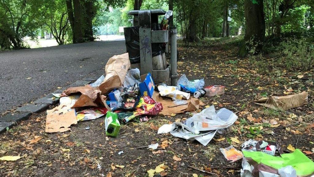 Müll liegt auf dem Boden neben einem Mülleimer. Vor allem sind Verpackungen zu erkennen.