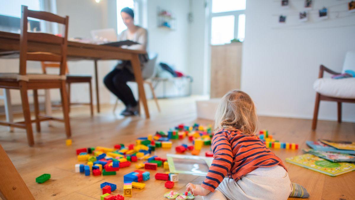 Ein Kind spielt auf dem Boden, die Mutter sitzt im Hintergrund am Computer.
