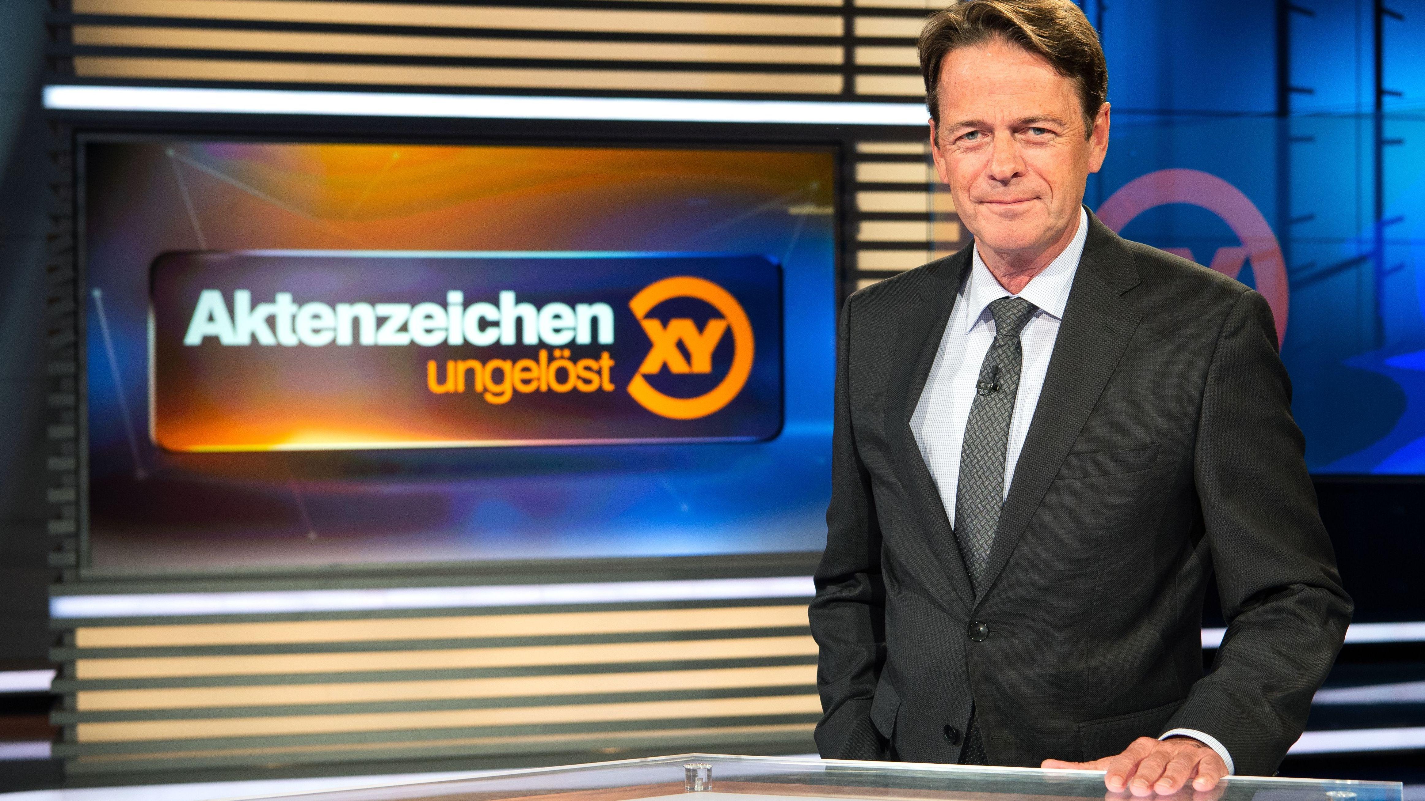 """Rudi Cerne im Studio vor dem Schild """"Aktenzeichen XY ... ungelöst"""""""