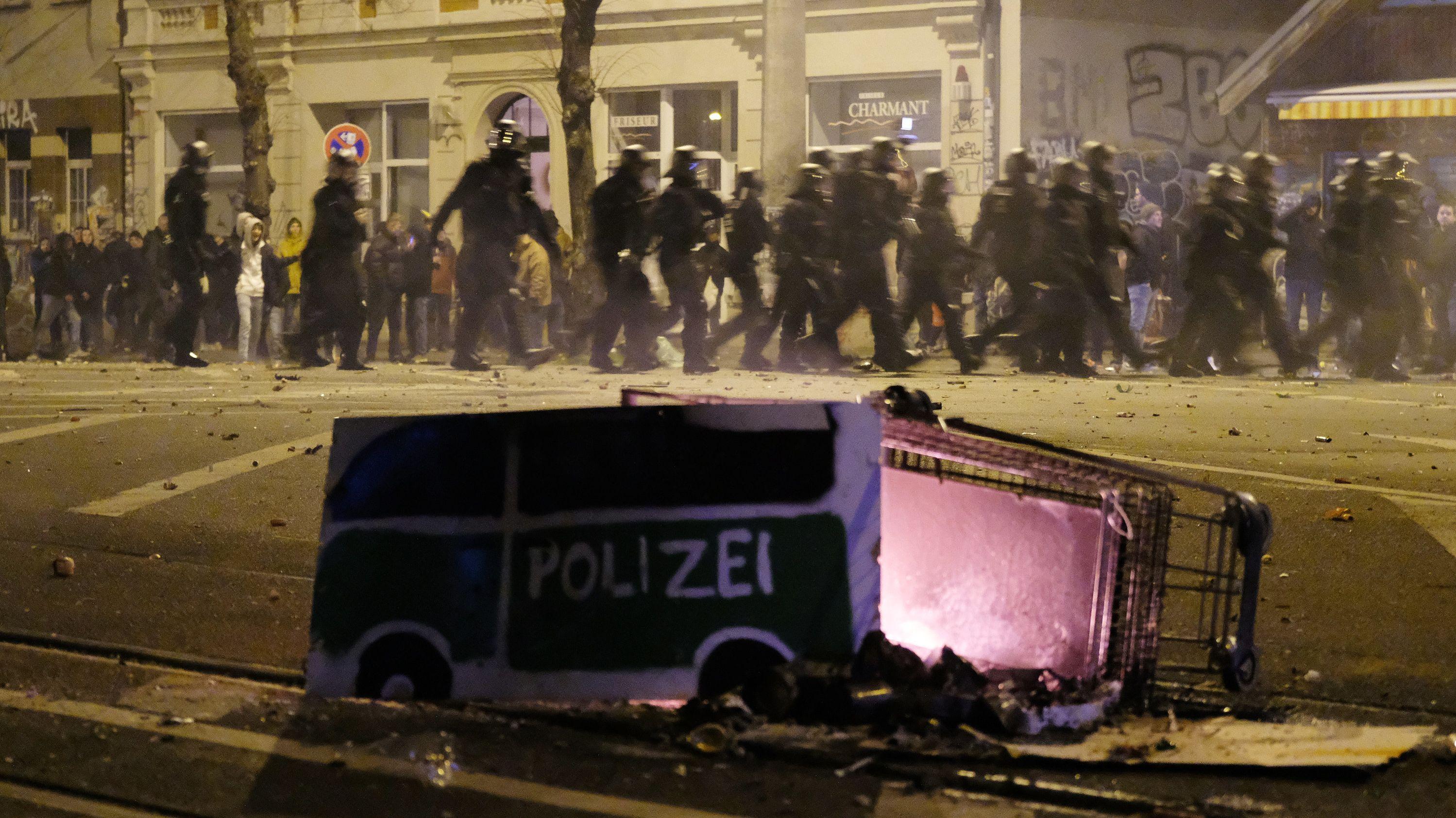 Polizisten räumen eine Kreuzung im Stadtteil Connewitz, während im Vordergrund ein Einkaufswagen liegt.