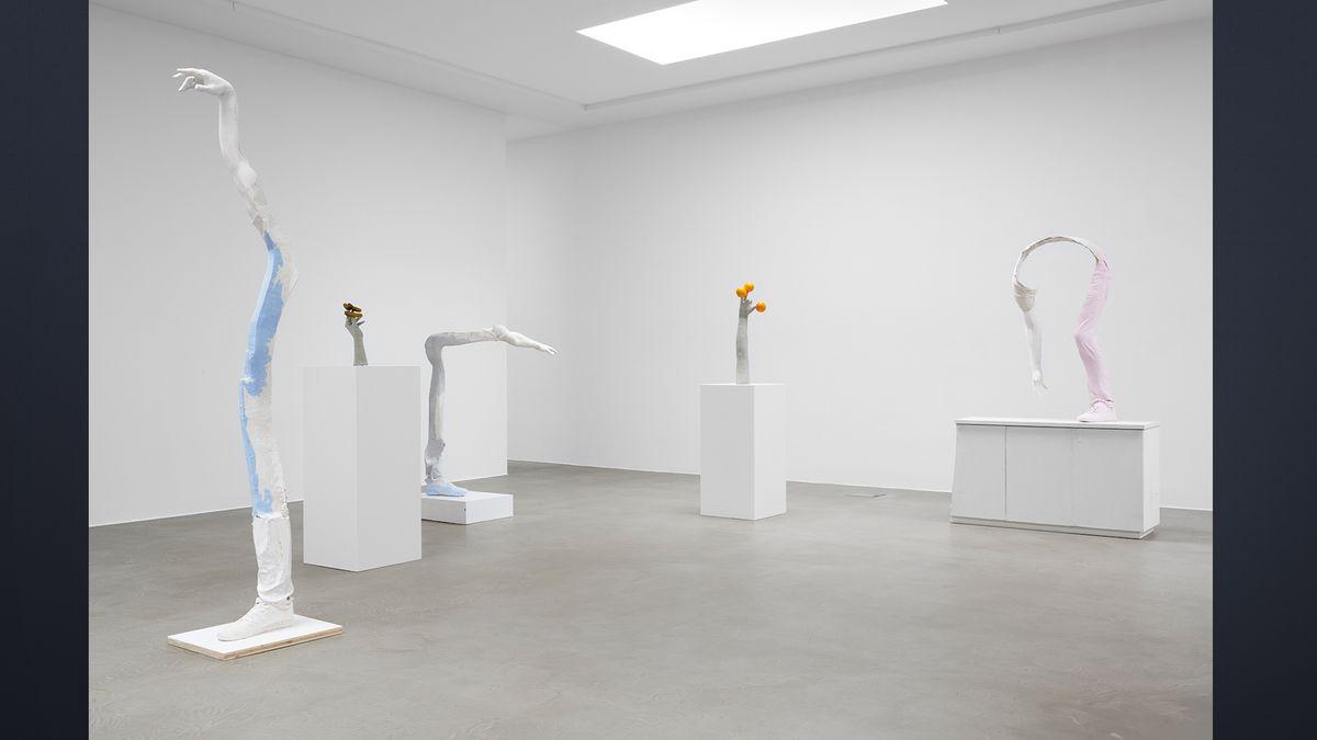 Weiße längliche Skulpturen, die nur aus Armen oder Arm und Bein verbunden bestehen, von Erwin Wurm
