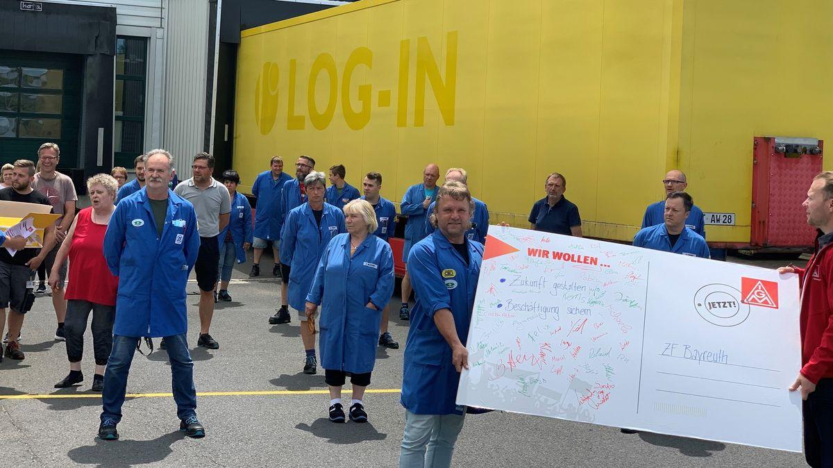 Beschäftigte des Automobilzulieferers ZF halten eine riesige Postkarte mit gesammelten Unterschriften hoch.