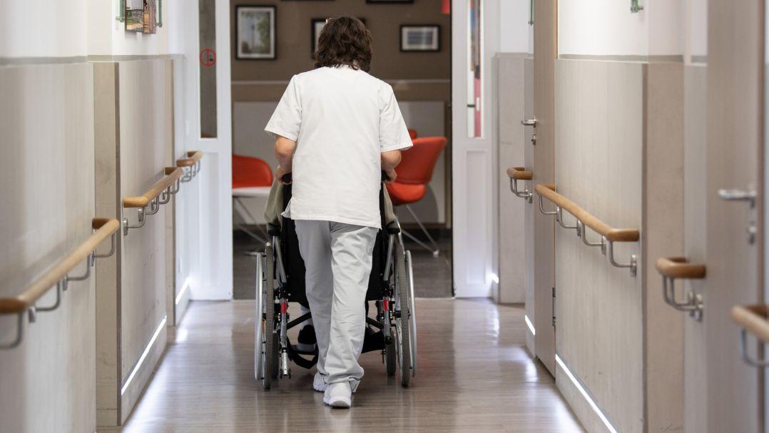 Eine Pflegerin schiebt eine Frau in ihrem Rollstuhl