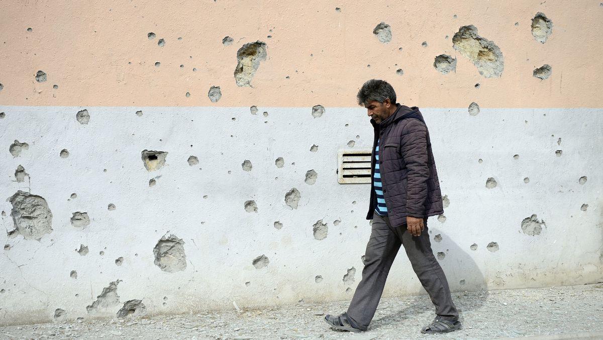 Ein Mann geht in Aserbaidscha an einer Hauswand vorbei, an der viele Einschusslöcher zu sehen sind.