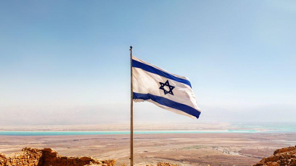 Die israelische Flagge vor einer Wüstenlandschaft in Israel