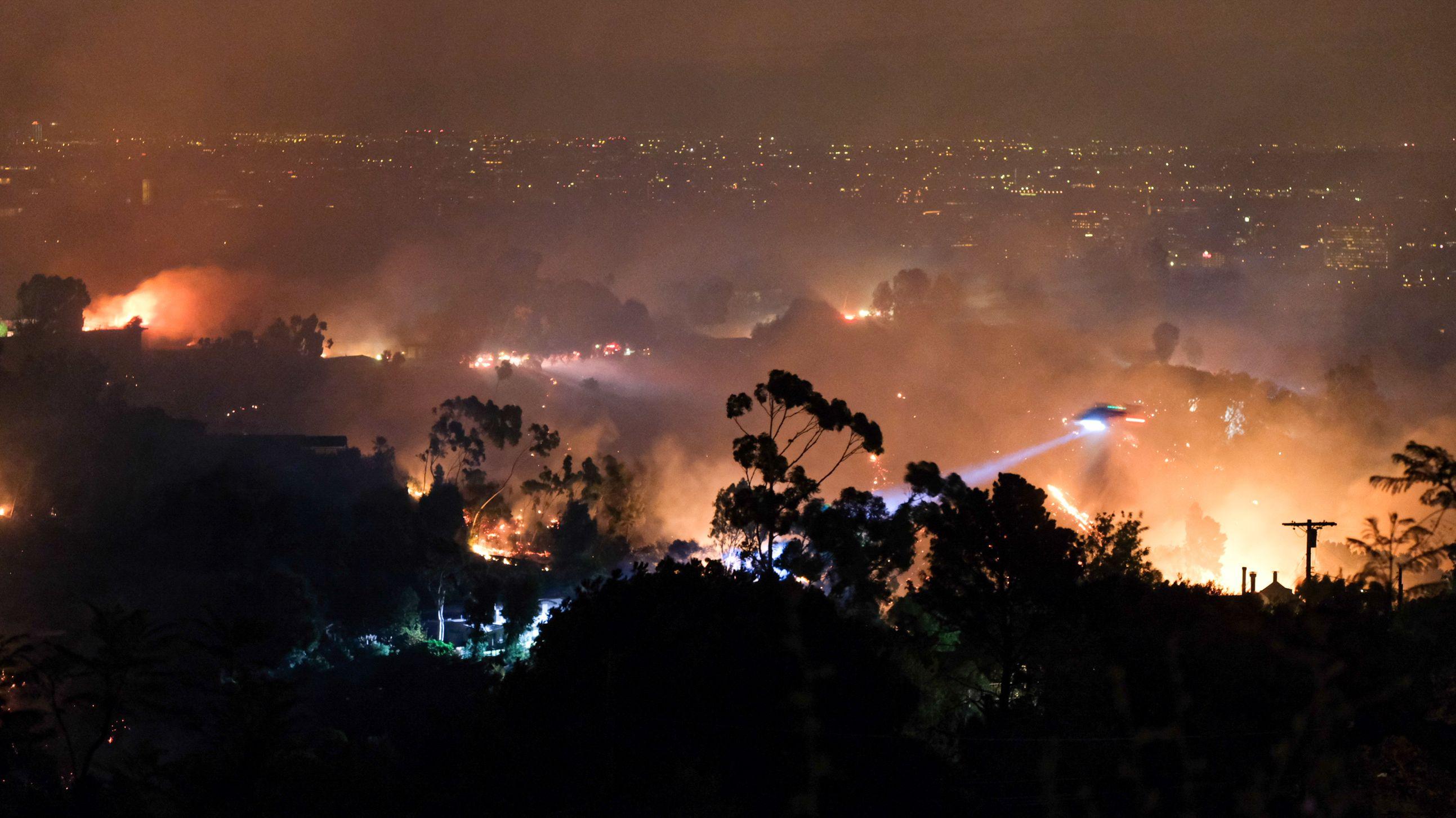 Los Angeles, Kalifornien: Ein Helikopter löscht in den frühen Morgenstunden von der Luft aus die Brände in den Bergen von Mandeville Canyon. Im Hintergrund sind die Lichter von Los Angeles zu sehen.