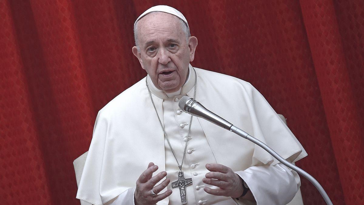 Papst Franziskus in weißem Gewand vor einem roten Vorhang