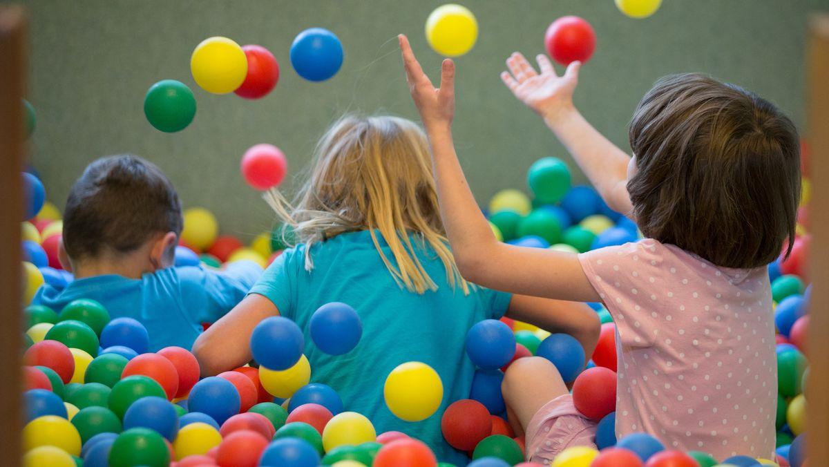 Kinder spielen in einem Bällebad in einer Kindertagesstätte.