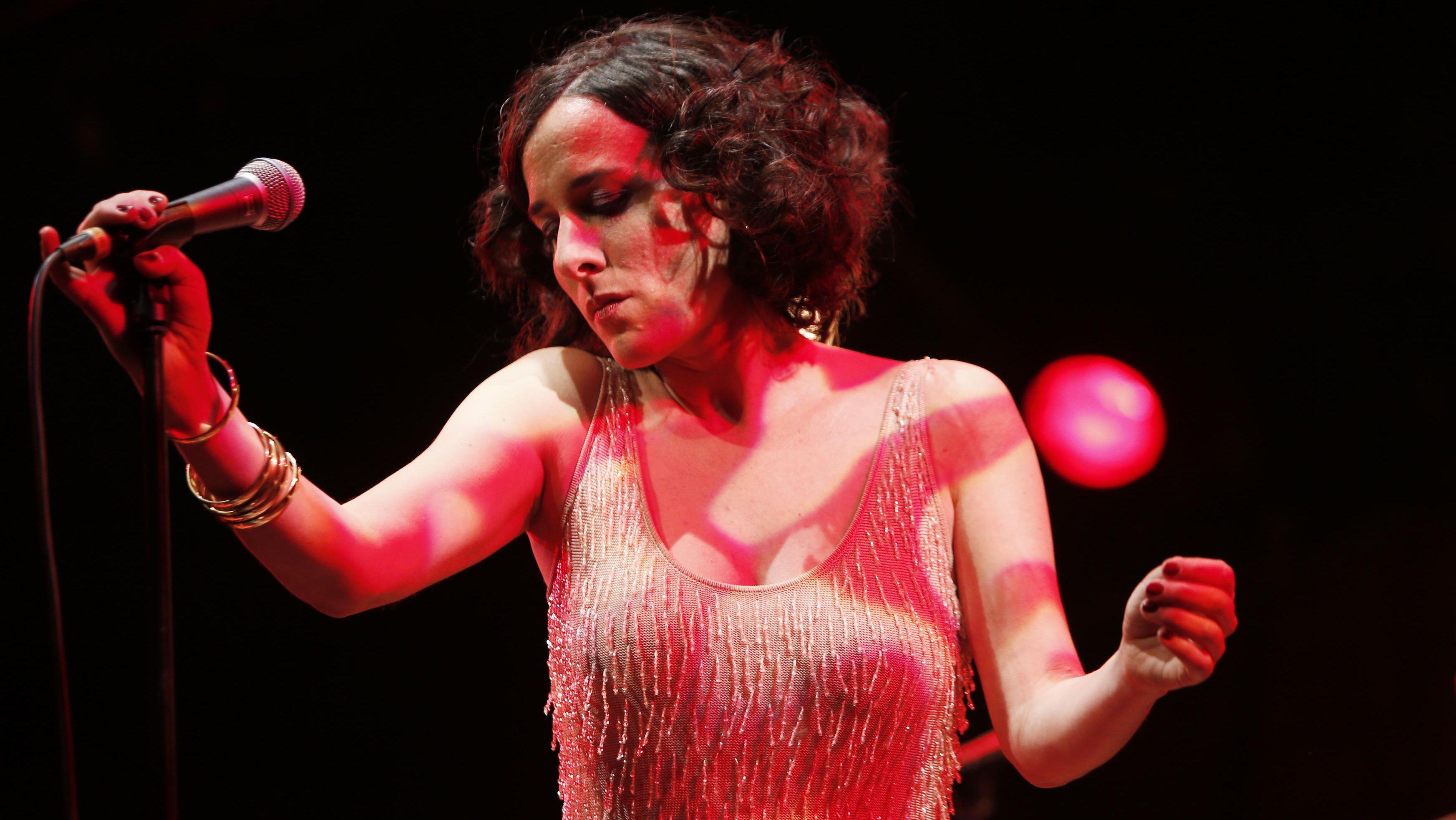 Die Musikerin Lisa Bassenge bei einem Liveauftritt in einem Pailettenkleid im roten Bühnenlicht