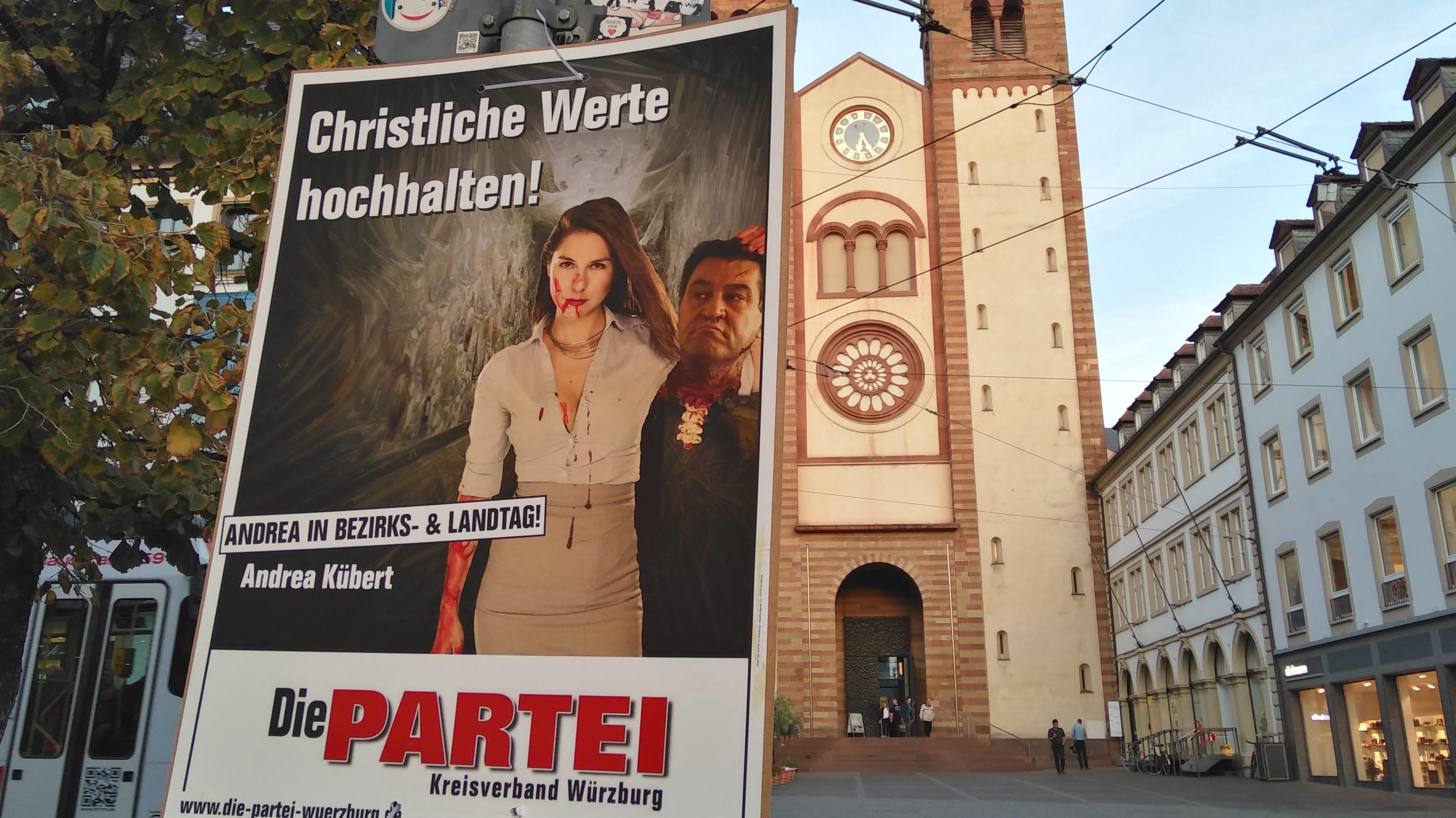 Wahlplakat mit geköpftem Söder vor dem Würzburger Dom