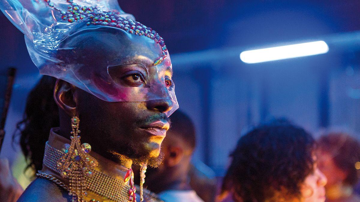 Ein Mann mit Bart, transparenter Gesichtsmaske, Ohrringen und Halsgeschmeide aus Katzengold blickt in die Ferne
