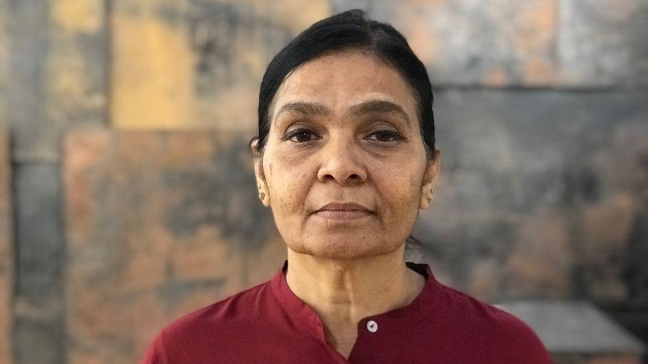 Porträt der indischen Künstlerin Sheela Gowda: Schwarze, streng nach hinten gebundene Haare, dunkle Augen, weinrote Bluse, konzentrierter Blick