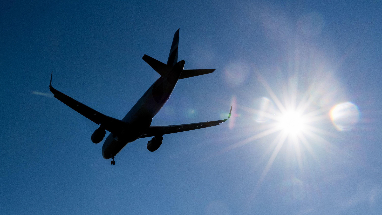 Flugzeug am Himmel mit blendender Sonne
