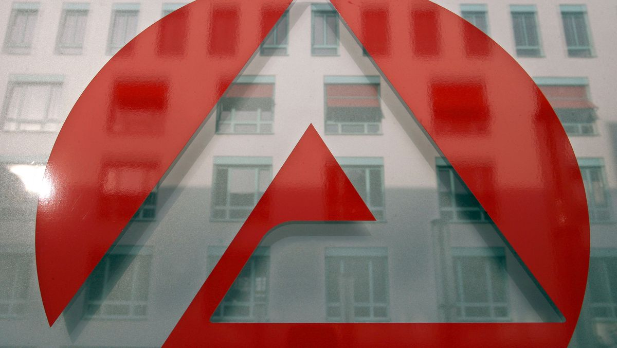 Das Gebäude der Agentur für Arbeit spiegelt sich in einem Schild, das das Logo der Agentur zeigt