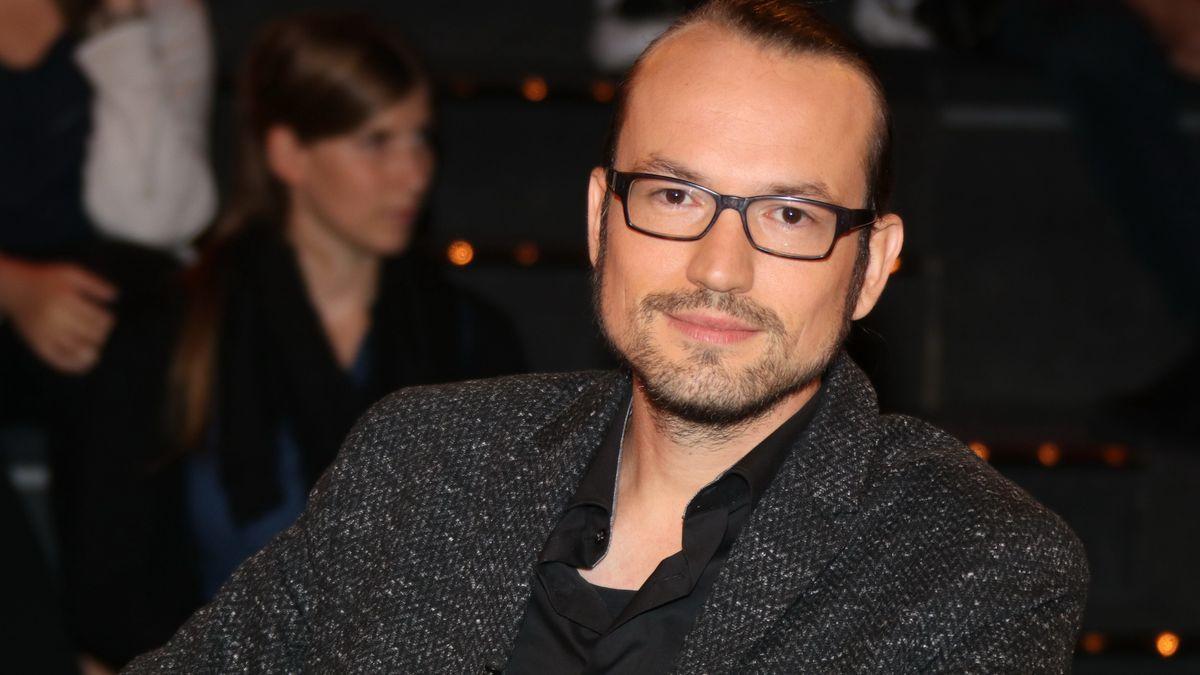 Porträt-Foto von Autor Jan Mohnhaupt mit markanter Brille und dunkelgrauem Mantel