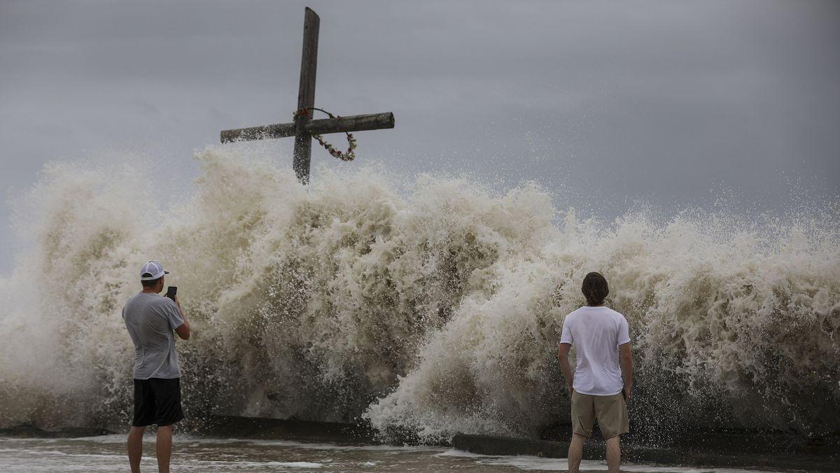 """Zwei Männer betrachten hohe Wellen, die als Vorboten von Hurrikan """"Laura"""" auf die Küste treffen"""