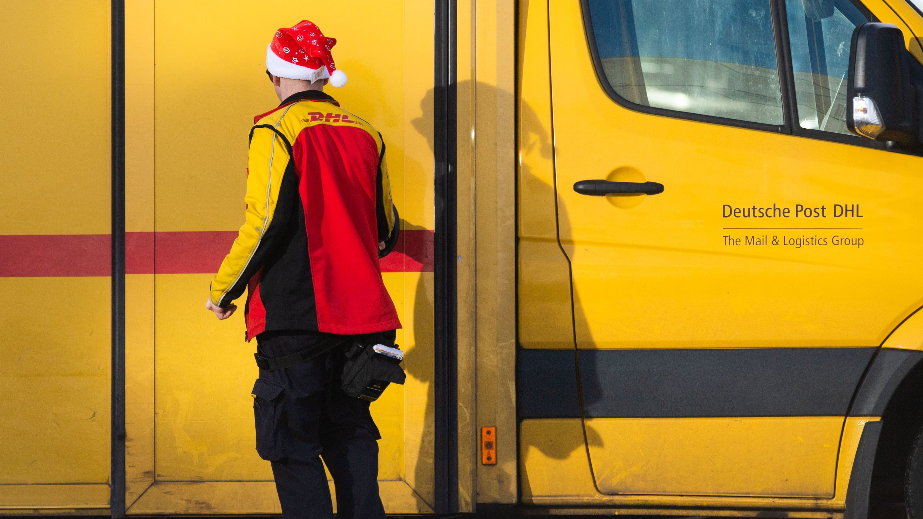 Ein Paketzusteller von Deutsche Post DHL trägt bei der Arbeit eine Weihnachtsmannmütze (Symbolbild).
