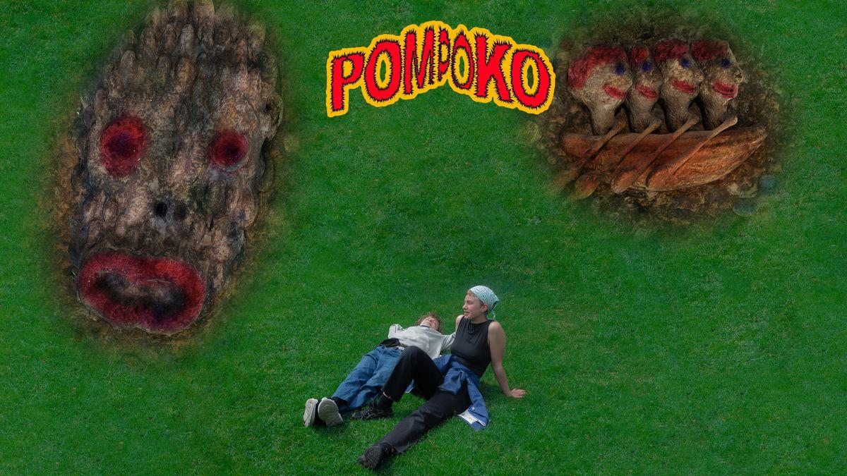 """Man sieht zwei Menschen auf einer Wiese sitzen, umgeben von einer gezeichneten unheimlichen Maske und  einem Ruderboot, in dem vier Fabelwesen sitzen. Es handelt sich um das Cover des neuen Pom-Poko-Albuns """"Cheater""""."""