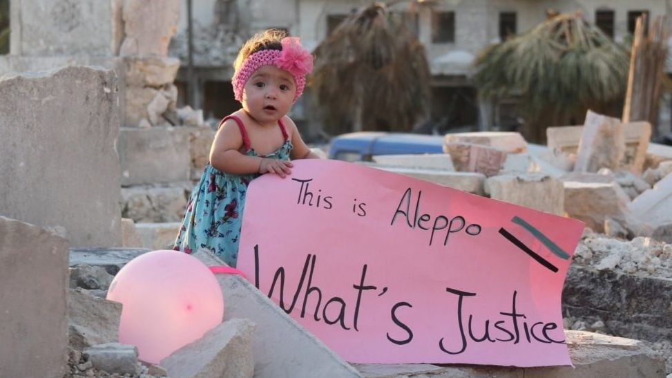 """Ein 2-jähriges Mädchen hält mitten in den Trümmern von Aleppo ein rosa Plakat mit der Aufschrift: """"This is Aleppo – What's Justice"""""""